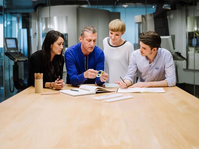 在最近出现的苹果招聘页面上,一个绝密的工业设计实验室照片作为其背景图片被曝光,而这据说是由Jony Ive领导的设计团队。   在照片中,四名苹果员工聚集在一张类似苹果商店的木制桌子的旁边讨论苹果智能手表的卡扣,桌子上是似乎是2款苹果智能手表的腕带。照片背景是玻璃墙,将工作区域和后面的电脑化铣床区隔开来。    苹果招聘页面曝光神秘工业设计实验室   这张照片与之前一份报告当中描述苹果工业设计实验室的布局非常相似,苹果工业设计实验室并非一般员工可以入内,只有那些直接与Jony Ive一起工作的员工才有