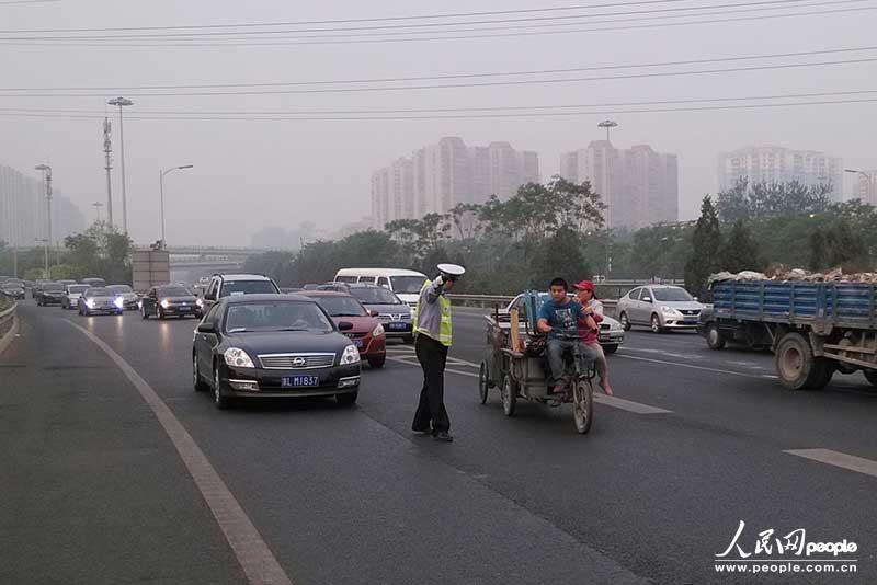早上6点李贵宾早已在京承高速巡逻,巡逻中发现一辆人力三轮,教育后,护送出高速路。(何建良摄)