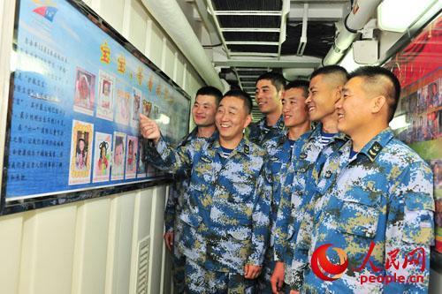 5月30日,临沂舰反潜部分士兵王东晓看着本人宝宝的相片,和战友们一同共享初为人父的高兴。熊利兵拍照