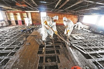 6月8日,清算职员在革除船舱地板 拍照/新华社记者 程敏