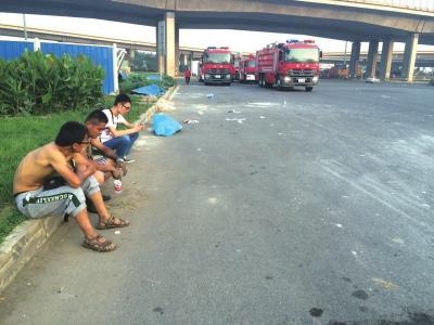 王芝春的遗体盖着蓝布单,躺在路边。京华时报记者 聂辉 摄
