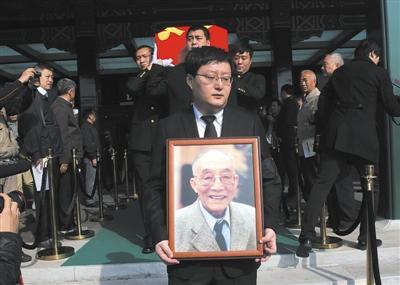 杜老的外孙杜帆捧着杜老的遗像走出礼堂,身后数人抬着杜老的遗体。本版图片/新京报记者 尹亚飞