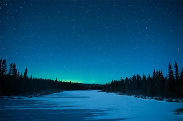 月光淡淡的打在湖面,远处看到微微的北极光 明尼苏达州