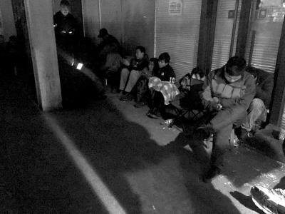 挂号人员蜷缩在门诊大楼外通宵排队。