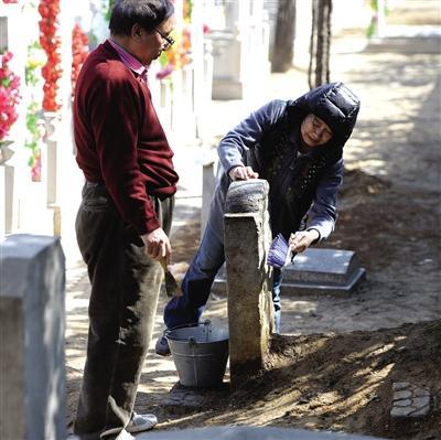昨日,八宝山人民公墓,祭扫者在清洗墓碑。