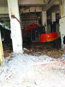 挖掘机开进门面房挖数个大坑 居民质疑要建地下室