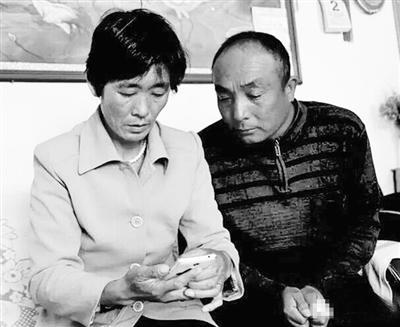 张朝花和丈夫张永忠,翻看手机里儿子的照片,成了她唯一的安慰。