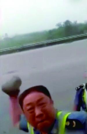 视频中一名穿制服男子拿起大块石头砸车窗玻璃。视频截图