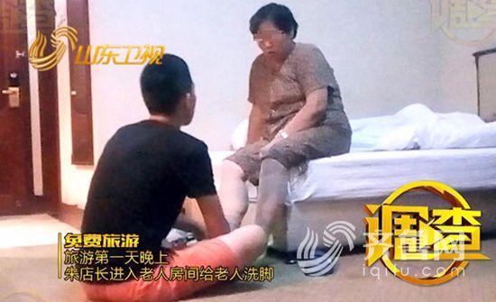 朱店长坐在地上给老人洗脚。视频截图