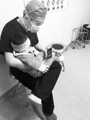 医生将孩儿抱在怀里抚慰心情
