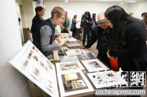 纽约市档案局工作人员向参与民众介绍照片保存。(侨报记者陈辰摄)