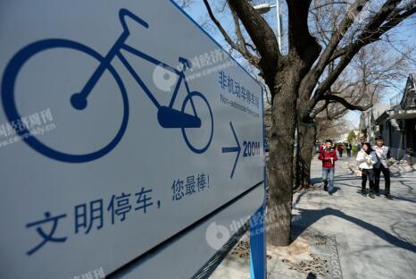 p48-1在共享单车出现之前,南北长街就已有规范自行车停放的政策。西城区划出10 条共享单车禁停道路后,记者实地走访发现,南北长街政策执行良好,整条大街上违停现象屈指可数。图为南长街上一座停车指示牌。