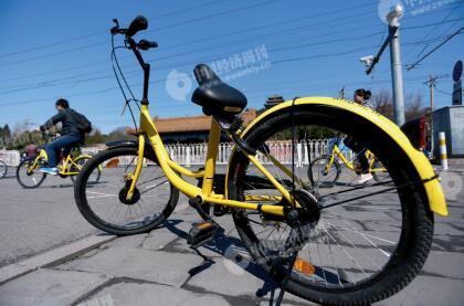 p47-3景山与故宫之间的景山前街,停放着一辆车座有损的共享单车。