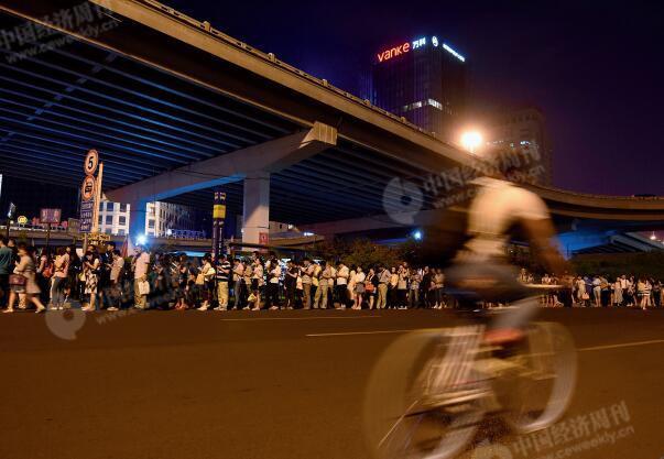 p48-1大北窑桥下开往燕郊的公交车站排起了长队。坐公交车是许多住在燕郊的上班族上下班的主要交通方式。