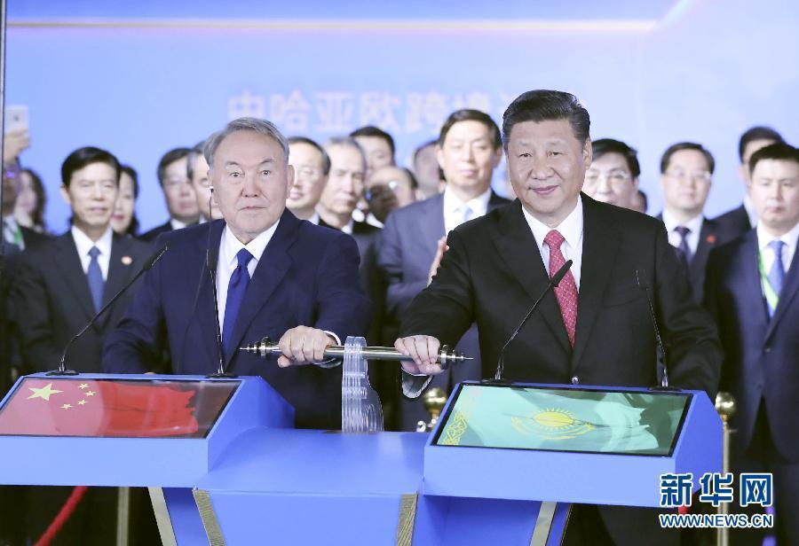 """6月8日,正在哈萨克斯坦访问的国家主席习近平在哈萨克斯坦总统纳扎尔巴耶夫陪同下,参观阿斯塔纳专项世博会中国国家馆,并共同出席中哈亚欧跨境运输视频连线仪式。这是在中国国家馆举行的中哈亚欧跨境运输视频连线仪式上,两国元首共同推动操控杆,视频显示中哈连云港物流合作基地和""""霍尔果斯-东大门""""经济特区无水港两个分会场四列火车鸣笛开行。新华社记者 丁林 摄"""