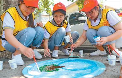 大学生给120多个井盖彩绘倡导节能环保等