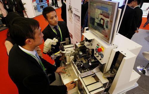 资料图:2017国际半导体展览会在上海开幕,一位展方工作人员(左)在向参观者演示一台半导体焊线机的操作。新华社记者 方�� 摄