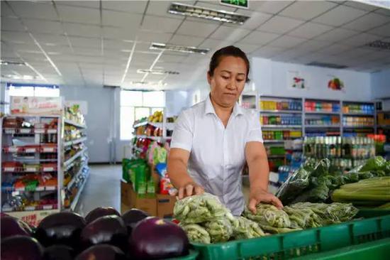 在内蒙古自治区锡林浩特市爱民社区,社区爱心超市营业员在整理蔬菜(7月21日摄)。新华社记者 连振 摄