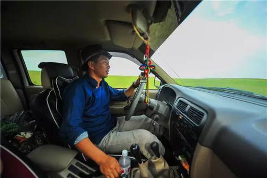 内蒙古自治区新巴尔虎右旗克尔伦苏木芒来嘎查党支部书记米吉格驾车行驶在牧场上(7月17日摄)。新华社记者 连振 摄
