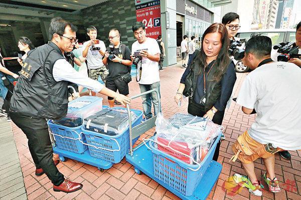 ■探员在投资公司内检走大批证物。 香港文汇报记者邓伟明 摄