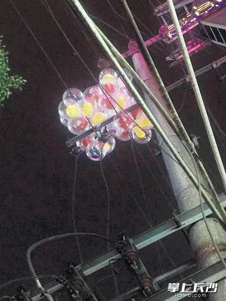 一大捧气球挂在电线杆的横梁上,取不下来了。