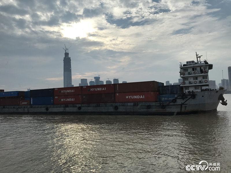 一艘满载集装箱的货轮沿江而下(孔华/摄)