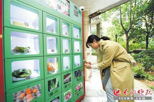 长沙某小区居民在家门口通过智能菜柜提取果蔬。长沙晚报记者 黄启晴 摄