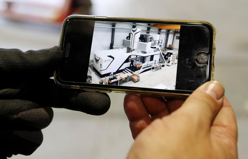 """德国工程师马丁·霍尔茨海德在安装现场用手机展示""""金牛座""""龙门铣床安装完成后的效果图"""
