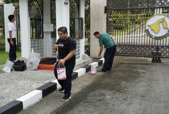 工人沙斯旺(中间)在努洛伊曼王宫大门外粉刷和清洗地面。新华社记者毕晓洋摄