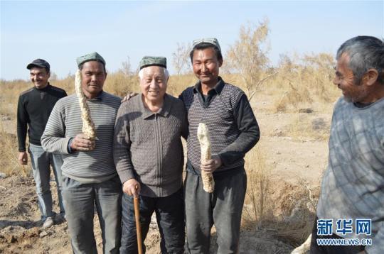 刘铭庭(左三)与老乡相符影(原料照片)。新华社发