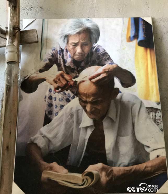 图为童汉芳母亲给正在浏览的父亲修整白发