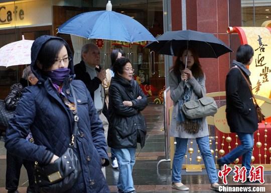 原料图:香港市民冒着蒙蒙幼雨出走。<p align=