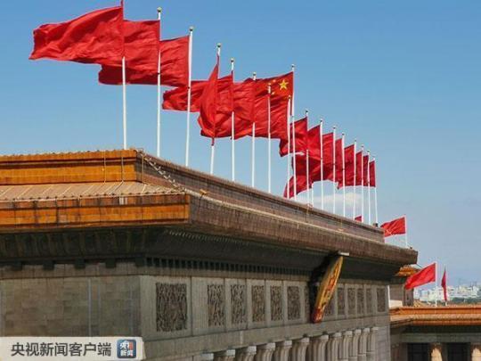人民大会堂东门上方迎风招展的红旗(央视记者张宇拍摄)