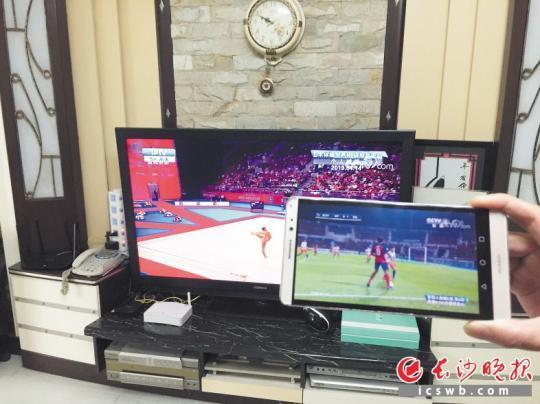 谭先生家,电视机与手机里的CCTV5频道播放的内容不一样。   长沙晚报全媒体记者 谢春年 摄