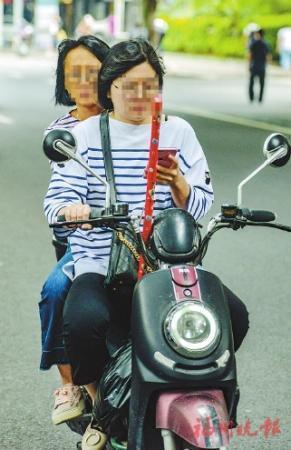 """电动自行车手看着手机上的成人和""""娃娃"""""""