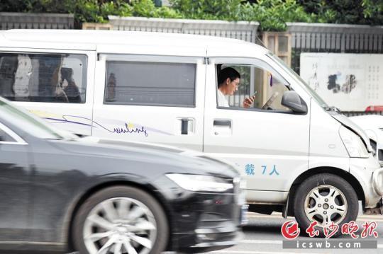 昨日早顶峰时段,营盘路上一位驾驶员正在驾车过程当中湾机。  均少山表报齐媒体记者 刘琦 摄