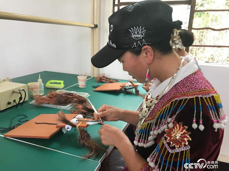 在每个黄豆大小的设备上穿10圈铜丝是40岁的侯景每天的工作。(记者 何川 摄)