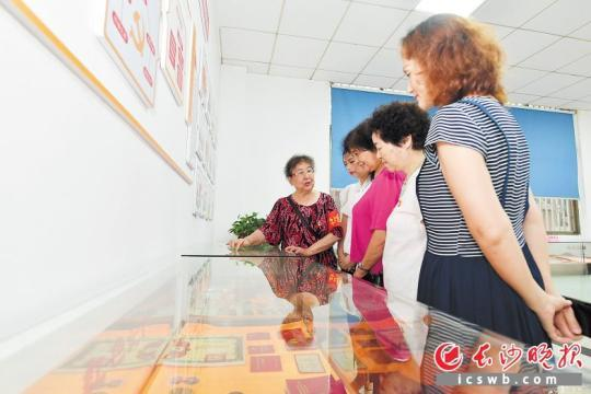 """""""中国大好人""""""""湖南省最美志愿者""""池凤英正在为旅行住民报告老物件的故事。 长沙晚报全媒体记者 王志伟 摄"""