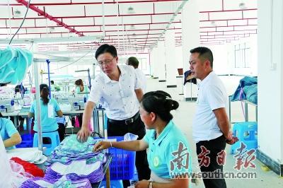 龙华区派驻东兰县干部、东兰县副县长陈毅强在青春制衣厂扶贫车间调研。