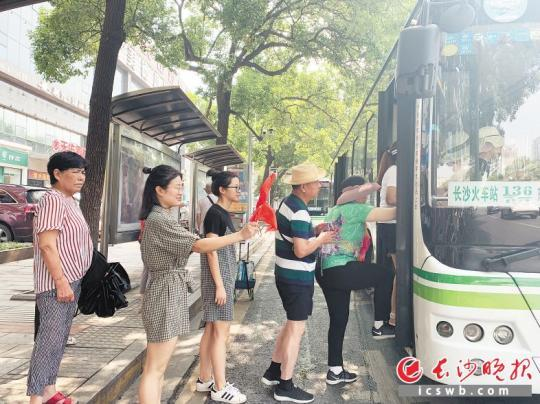 ←正在韭菜园街讲蓉园路心公交趁魅站,市平易近又跪列队上公交车。