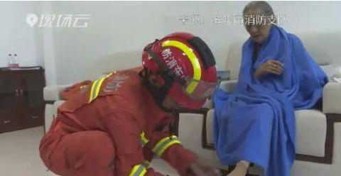 9旬白叟被困火中,救火员救出后借帮她换上清洁袜子