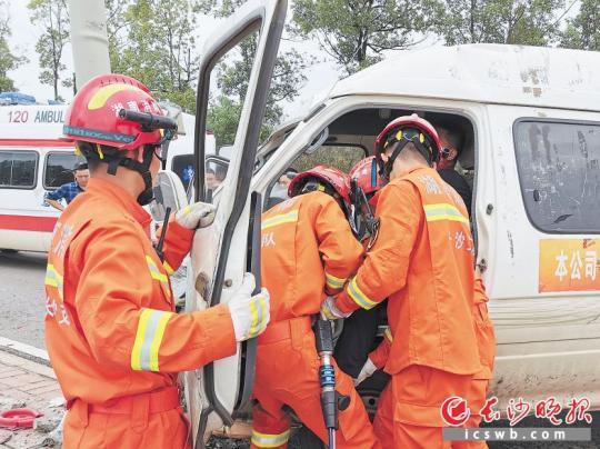 现场,消防指战员对面包车内的被困司机实施救援。长沙经开区消防救援大队供图