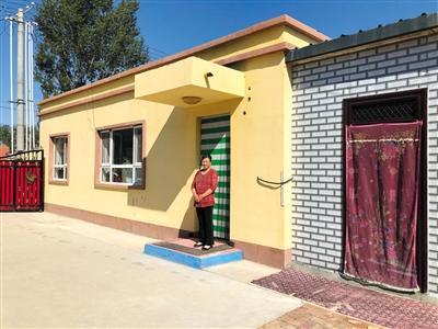 叶里斯南也肯村村民兰英英站在自家新建的抗震安居房前。本版摄影/新京报记者 周依