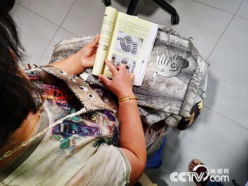 """王海珠根据书上的""""海东青图案""""缝制鱼皮衣上的图案。(何川 摄)"""