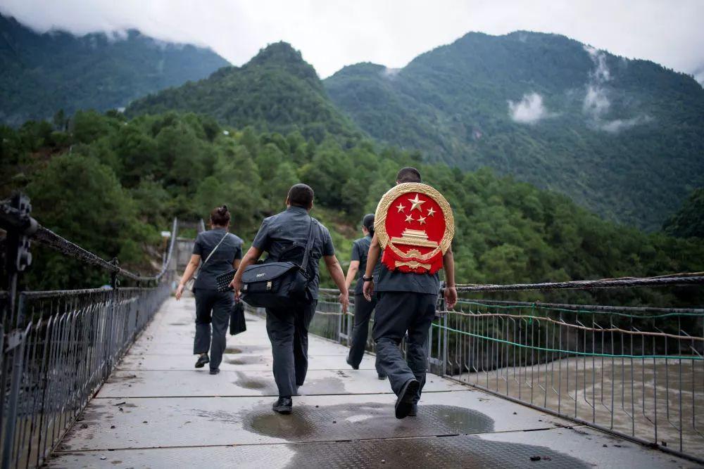 攀高山、过索桥、躲落石……他每年要背着国徽步行近万公里