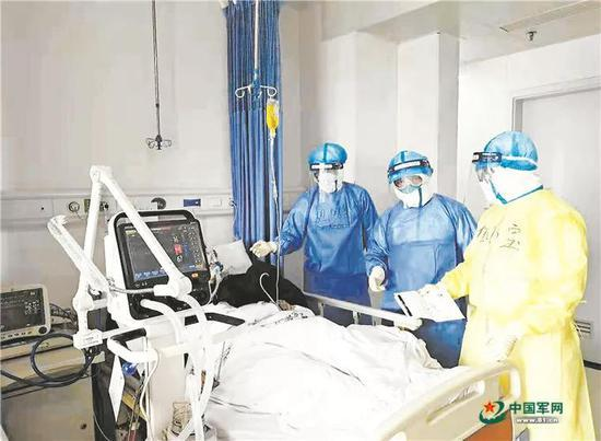 1月29日,医疗队专家李琦与同事在病房内查房,讨论治疗方案。于方洲 摄