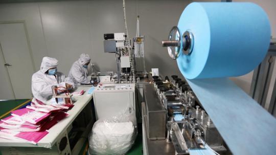 2月9日,在河南省焦作市康业医用材料有限公司生产车间,工人在生产口罩。