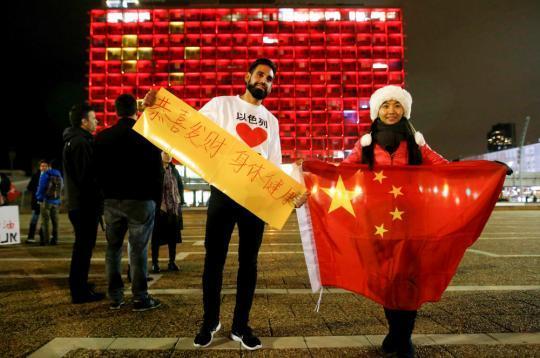 2月11日,在以色列特拉维夫市政大楼前,在以华人和以民众表达对中国的祝福。新华社发(吉尔·科恩·马根摄)