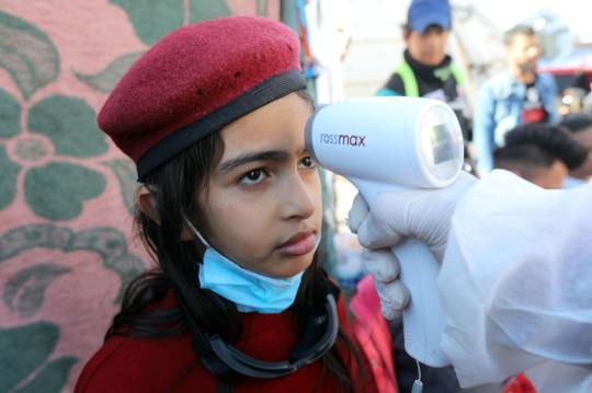 3月2日,在伊拉克巴格达解放广场,一名女孩接受体温检测。新华社发(哈利勒·达伍德摄)