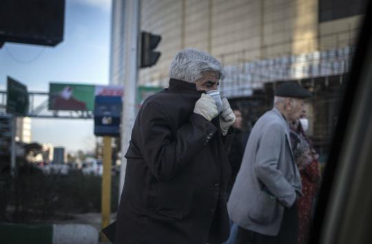 3月2日,在伊朗德黑兰,一名男子戴着口罩出行。新华社发(艾哈迈德·哈拉比萨斯 摄)